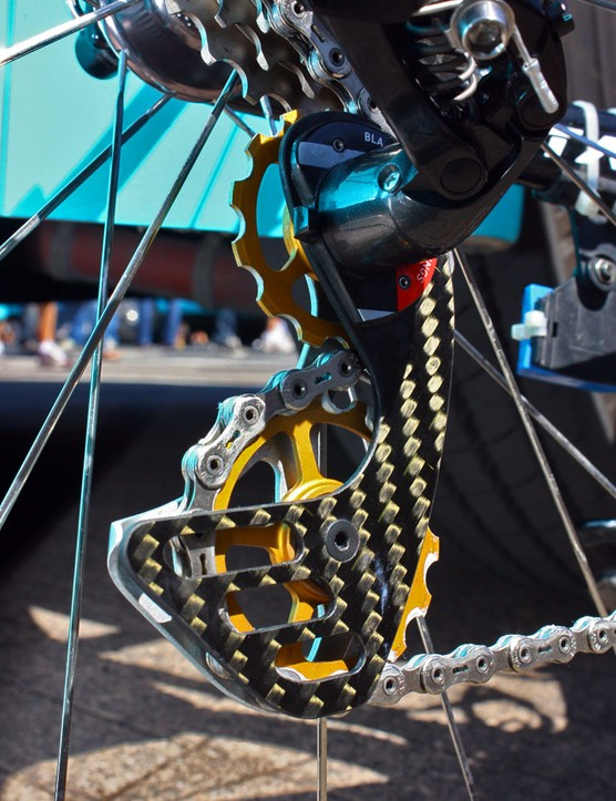 The custom derailleur cage attaches to the original cage's hacked-off stub.