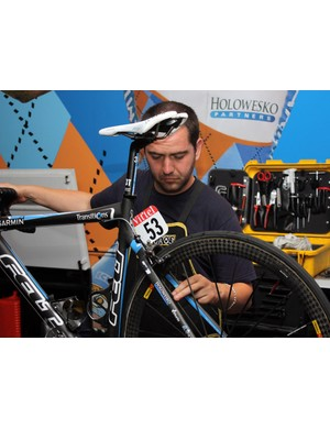 Inaki Goiburu checks the adjustment of Tyler Farrar's brakes.