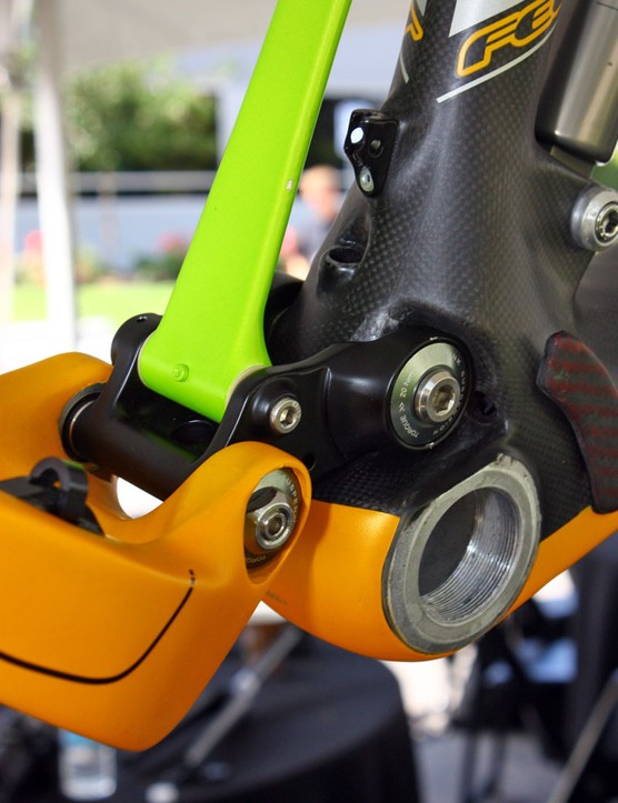 The rear derailleur housing exits the main frame just ahead of the lower link pivot.