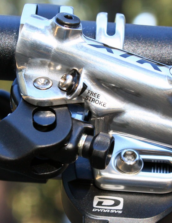 The 'Free Stroke' screw adjusts the top-out position of the master cylinder piston, effectively allowing users to customize lever throw