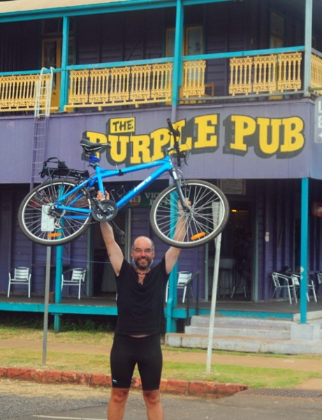 Mike Laird celebrates the end of his epic solo cycle ride across Australia in Normanton, Queensland
