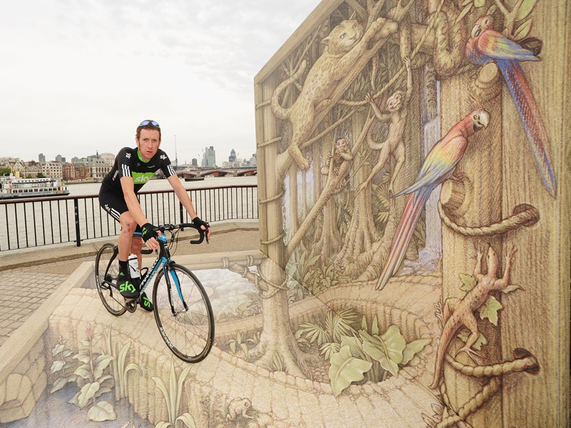 Bradley Wiggins and his Sky team-mates will be donning rainforest-themed kit during this year's Tour of Britain. Here he poses next to a specially commissioned artwork by 3D artist Kurt Wenner