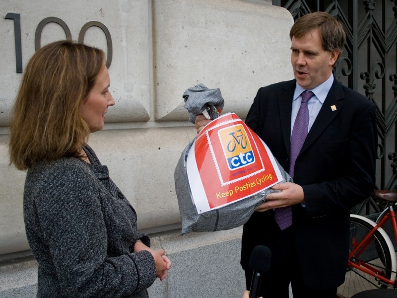 Kevin Mayne of CTC hands protest letters to a representative of Royal Mail