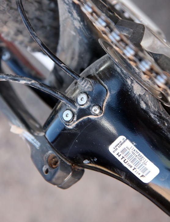 The removable plate on the underside of the bottom bracket makes it easier to fish the lines through the exit ports. An additional clamp secures the rear brake hose to keep it from migrating inside the down tube