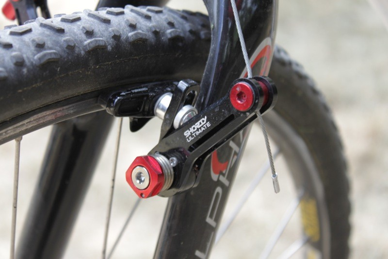 The straddle cable pinch bolt is captured within the brake arm