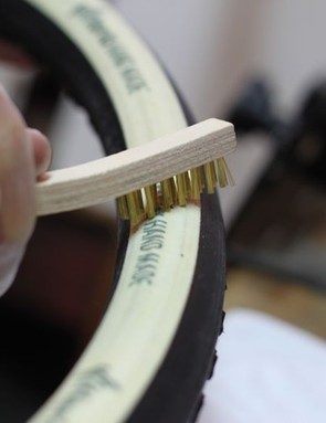 Prepping a coated base tape with a small wire brush; after brushing the tape it is wiped down with acetone