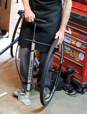Inflate the tire to 20psi to true. Then, after setting the base tape with a broomstick or square edge, inflate it to its maximum recommended psi for the 24-hour curing period