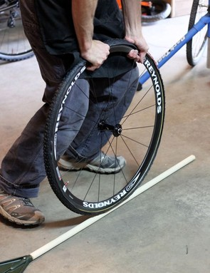Use a broomstick or rake handle to push the base tape into the rim bed after the tire is true