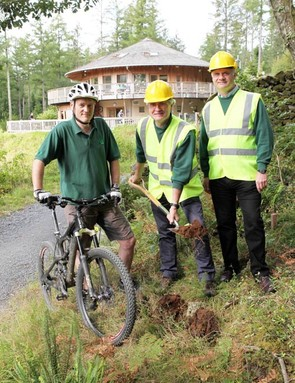 The Director General of the Forestry Commission, Tim Rollinson, turns the first sod on the new trail watched by Mountain Bike Ranger Andy Braund (left) and Forestry Commission Wales Director Trefor Owen.