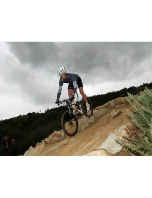 Cannondale rider Paul Beales demonstrates one of the man-made features on the Olympic mountain bike course at Hadleigh Farm in Essex