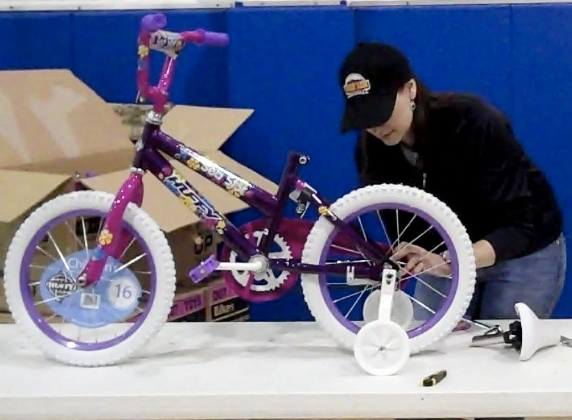 Jennifer Cox, the associate brand manager for Tender Ridge Angus beef, assembles a 16-inch girl's bicycle. The donation included 16-, 20-, and 24-inch bicycles for boys and girls