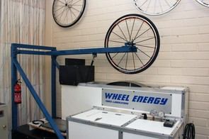 Test tires are mounted on control wheels and applied to the rotating drum with hydraulically controlled pressure