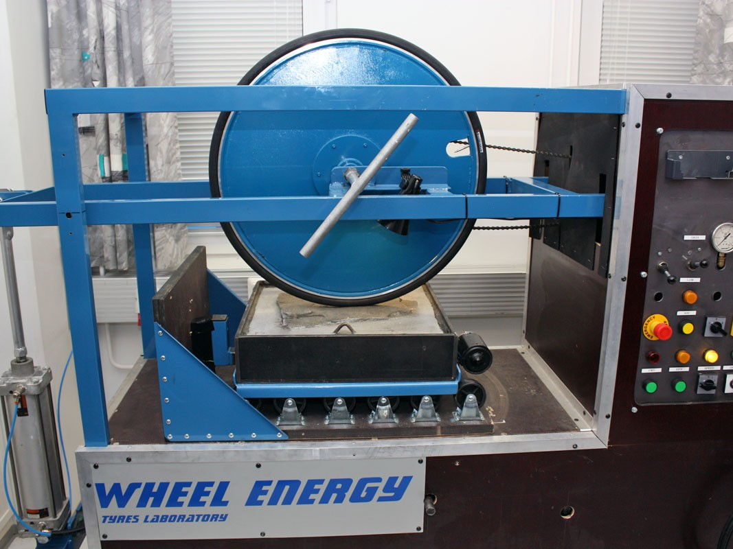 Tire friction is tested by controllably moving a small section of road material against a stationary wheel