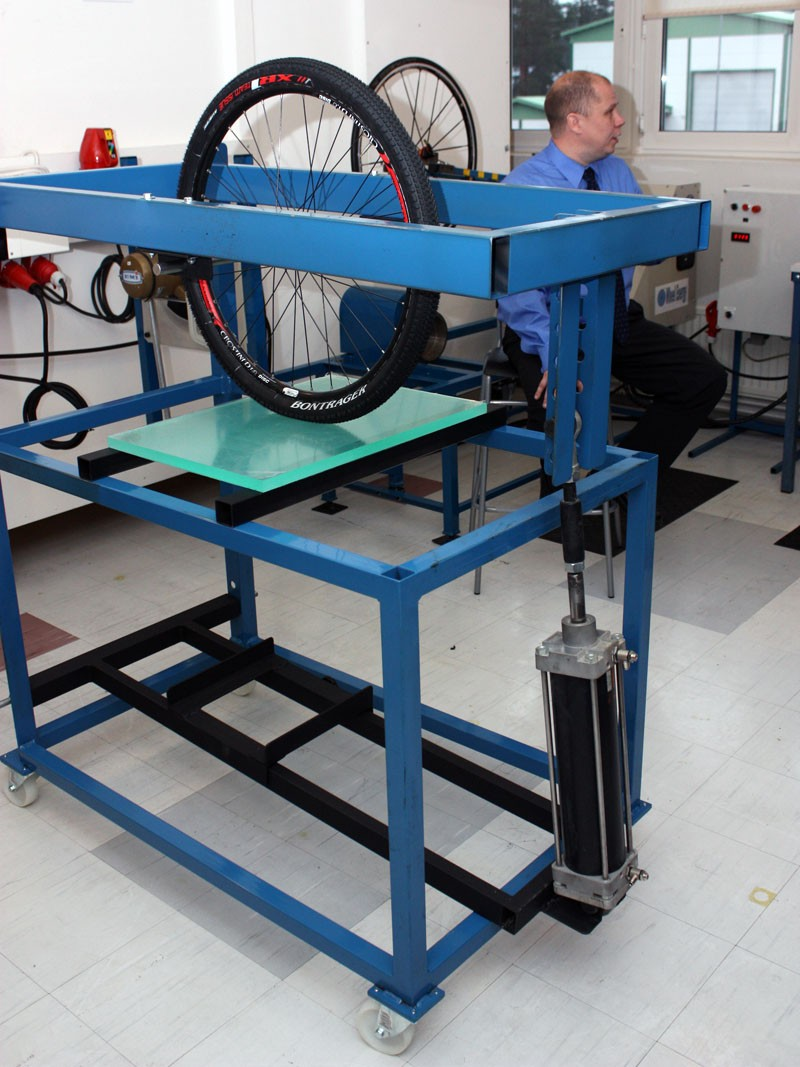 The tire contact patch test station incorporates a hydraulic cylinder to apply a consistent load