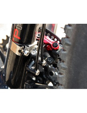 The backside of the front derailleur shows the hose connections and the hydraulic piston
