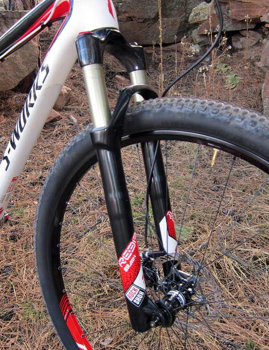 The Specialized/RockShox Reba S29 fork uses upper tubes, lower legs, and air spring internals from RockShox while Specialized adds its own carbon fiber crown and steerer and inertia-valve damper