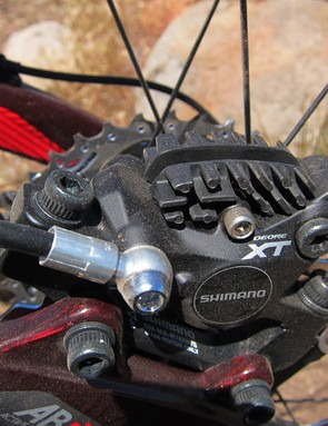Shimano's revamped Deore XT brake caliper uses a two-piece forged aluminum body with advanced heat management features that include 22mm-diameter ceramic pistons and finned brake pads