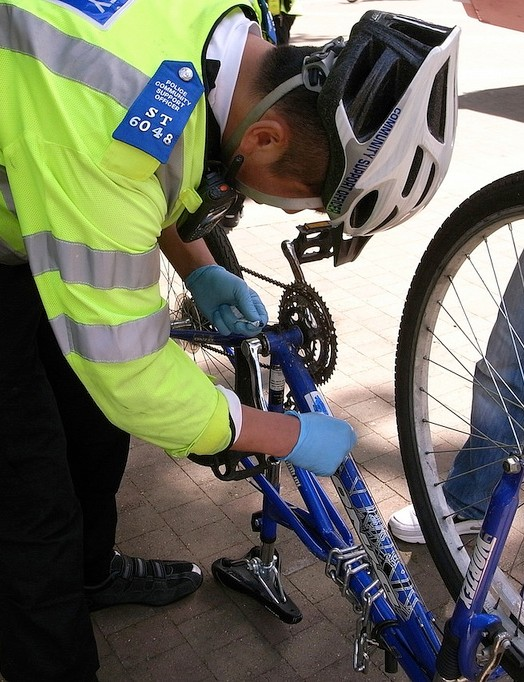 A member of the Cycle Task Force applies the BikeRegister security mark to a bike