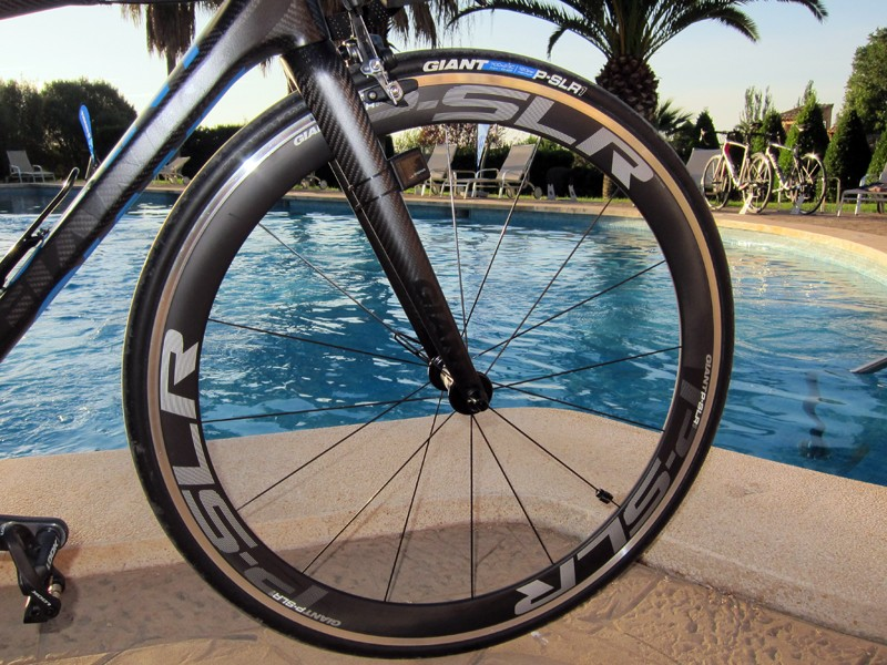 Giant is jumping into the pre-built road wheel market with two models.  The P-SLR1 Aero features a 49mm-deep scandium-enhanced aluminum and carbon fiber clincher wide-profile rim, bladed straight-pull stainless steel spokes, DT Swiss hub internals and extra-wide spoke flanges that notably boost lateral rigidity.  Claimed weight is just 1,575g for the pair.
