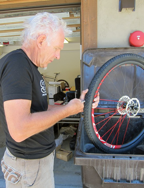 Specialized team mechanic Sandy Gilchrist trims half the center knobs off a rear Fast Trak LK tire for better grip on the short track's gravelly corners