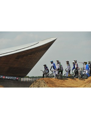 BMX riders are pictured in front of the velodrome (L) during a practice session at the Olympic BMX course