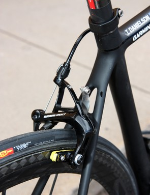 A stainless steel number holder is sandwiched in between the SRAM Black Red rear brake and the seat stay bridge.