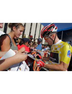 Overall race leader Levi Leipheimer (L) of the USA riding for Team Radio Shack signs autographs for fans before the start of Stage Two from Gunnison to Aspen of the 2011 USA Pro Cycling Challenge on August 24, 2011 in Gunnison, Colorado