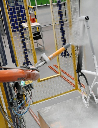A pricepoint hardtail is sprayed with its clear coat by Orbea's automated paint system