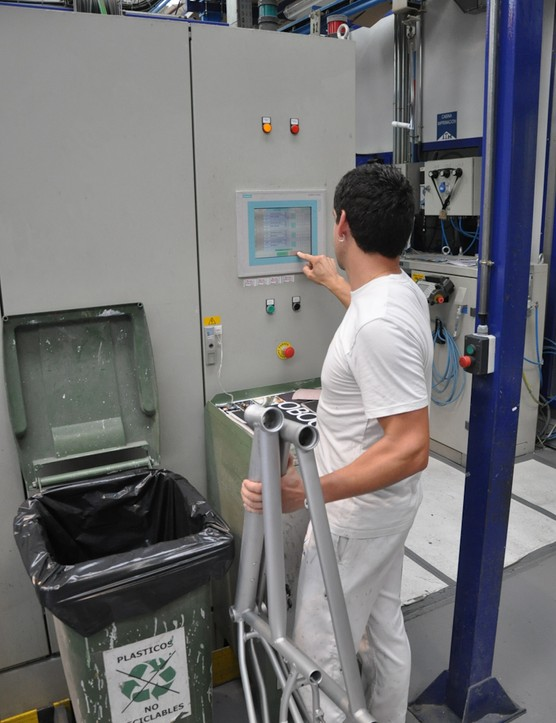 An Orbea employee demonstrates the automated paint system
