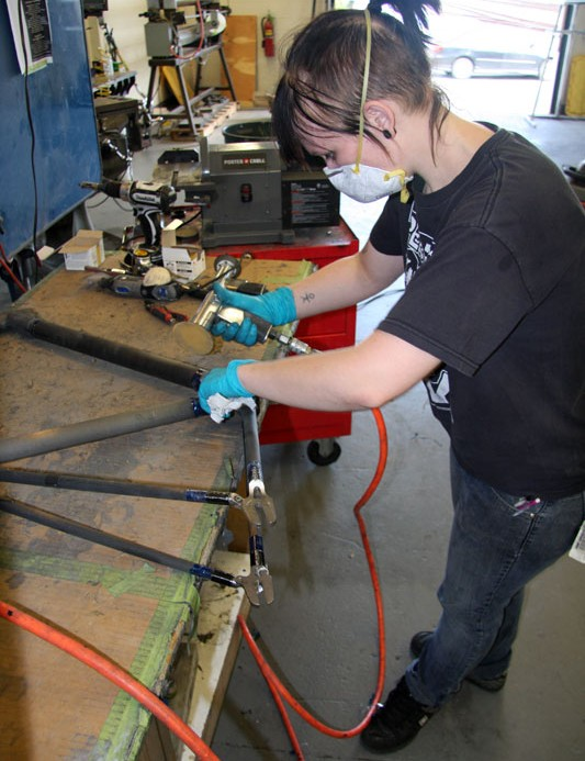 A frame is lightly sanded in preparation for painting