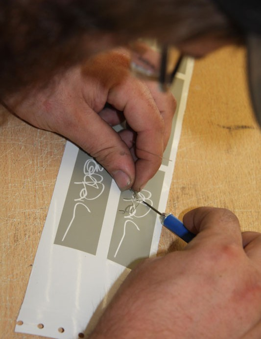 A worker cuts out the Bob Parlee signature decal for placement on the chainstay