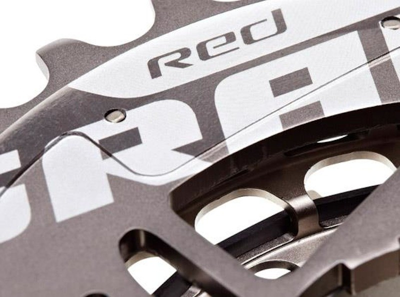 The backside of the new XG-1090 SRAM Red cassette uses an aluminum innermost cog that's press-fit on the rest of the machined steel structure. That black polymer band embedded in the trough of the two visible cogs is likely being used to quell drivetrain noise