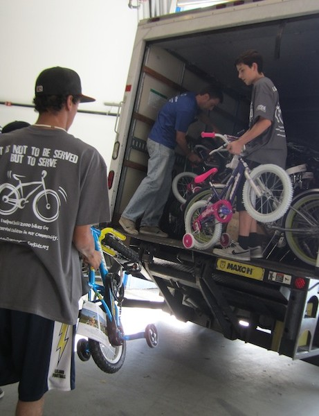 Darren DeMonsi, with Campbell-based EMC Families First, picks up bicycles that were among 2,400 assembled by More than 800 volunteers at TurningWheels for Kids' 2011 Big Bike Build on Dec. 10, 2011. He gets a hand from volunteers (from left) Josh Nashed, Zach Doxie and Brett Vranich, an Almaden resident