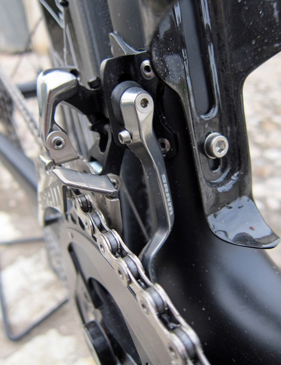 The small adjuster screw just to the left of the mounting bolt both adjusts the position of the chain catcher and fixes it in place