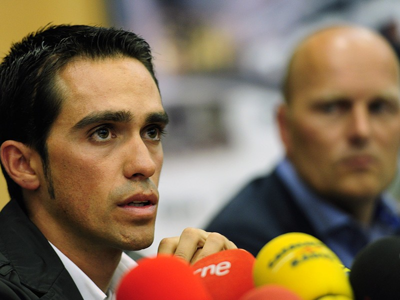 Alberto Contador looks on next to Team Saxo Bank general manager Bjarne Riis during a press conference a day after the court of arbitration for sport handed him a two-year ban and stripped him of his 2010 Tour de France title following a positive test for clenbuterol