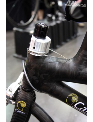 Cables connect the center-mounted bars to the front-mounted steerer on this wild Calfee tandem.