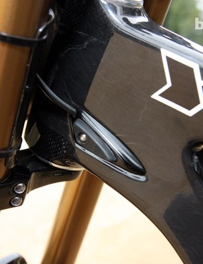 The rear derailleur housing and rear brake hose are internally routed through the carbon fiber main triangle. Fork stops are built in as well. Note the woven carbon fiber reinforcement layers around the ends of the head tube