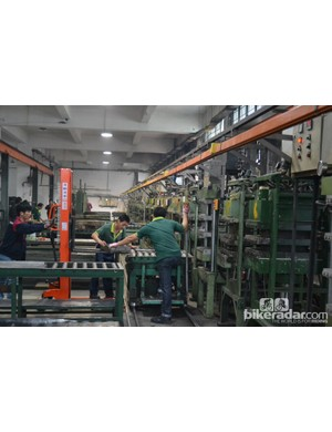A row of curing machines with one component mould being loaded. The moulds are very heavy so they aren't carried by hand. When all the machines are running the temperature in this room often exceeds 40C