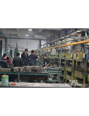 It doesn't usually take this many people to lay a frame into a mould but this one is a 2013 pre-production prototype and they're testing the process