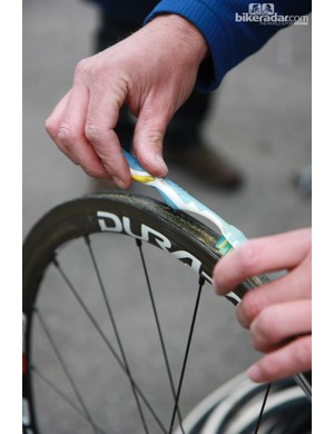 After the glue is applied, this Rabobank mechanic spreads it out on the tire bed with an old toothbrush that's soaked in solvent. The solvent keeps the brush from getting gummy and also makes the glue easier to spread in a thin layer