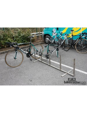 Teams often use racks like this to stage bikes. It's a compact setup that can hold either complete bikes or bikes with the wheels removed. It also automatically ensures all the bikes are neatly lined up for photos