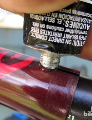 Hold the tube of silicone adhesive tightly against the seat tube slot and work from the bottom up until the void is completely filled