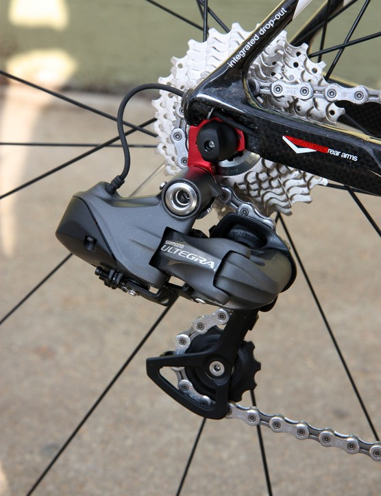 The rear derailleur cable (or wire in this case) runs through the chainstay