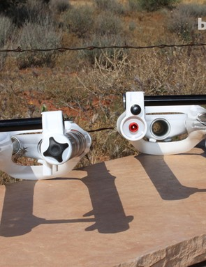 The 26in fork's lowers (left) integrate the rebound knob (red) and a bumper on the right as protection, where as on the 29in fork (right) the rebound knob is recessed and the bumpers are forward on the offset dropouts