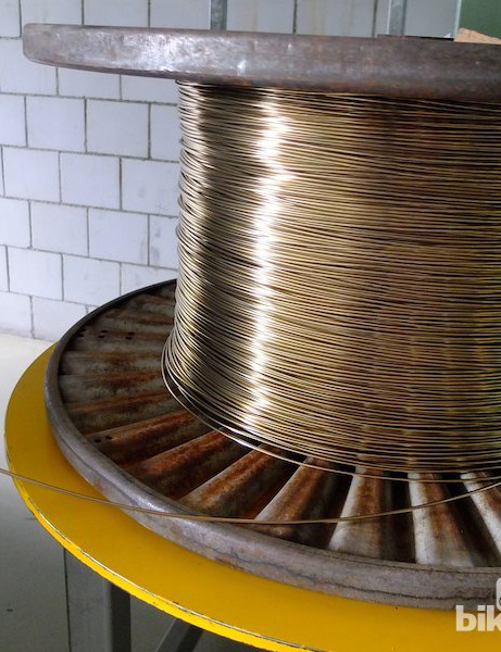 A huge reel of brass wire that's formed into spoke nipples