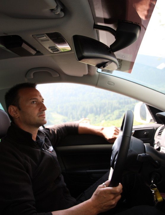 Driver Dario Acquaroli watches attentively in the rearview mirror during the stage. Action is happening on all sides and situational awareness is critical.