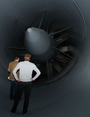 People standing inside the tunnel give scale to the size of the facility