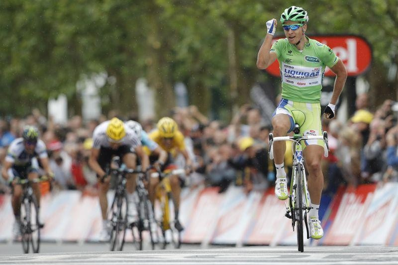 Peter Sagan crosses the line to win stage 3, doing a running man impression, a la Forrest Gump.