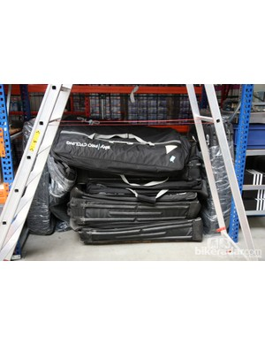 Soft-sided bike travel cases from British company DHB are piled up in one area of the service course