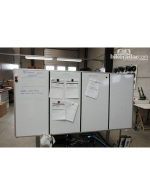 Whiteboards in the mechanics' area include important notes for equipment flow, pending tasks and other communications